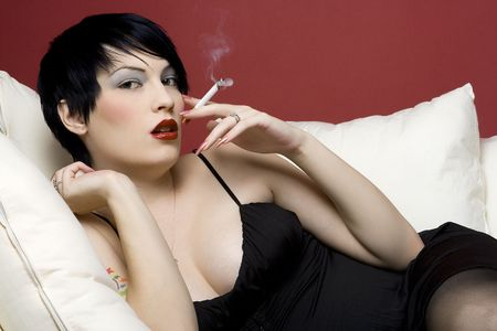 Woman smoking a cigarette on white sofa.