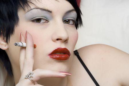 trashy: Woman smoking a cigarette on white sofa.