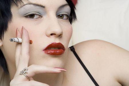 Woman smoking a cigarette on white sofa. photo