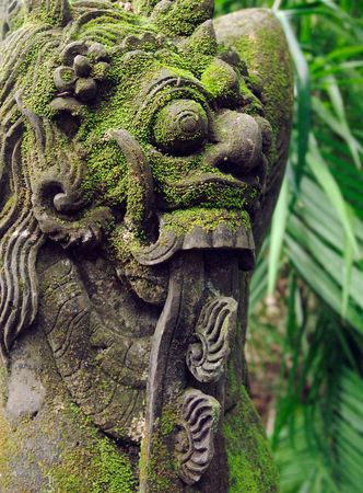 Bright green moss on menacing stone carving
