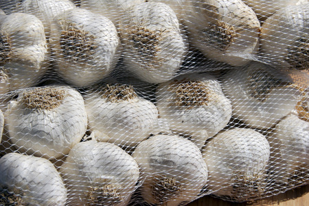 Mesh bags filled with fresh bulbs of garlic