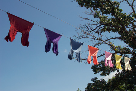 Colorful shirts hanging on clothesline against blue sky photo