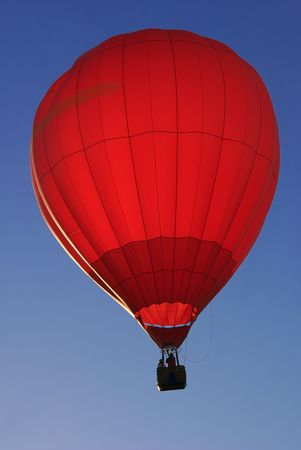 iluminate: Red hot air balloon illuminated by sunrise against blue sky