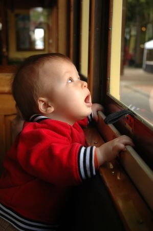Little boy looking with amusement at streetcar window Stock Photo