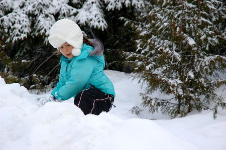 Little girl in white fur hat, blue jacket and black snow pants climbing on a show hill photo