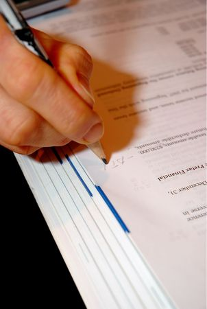 Hand of a person making marks in a financial textbook