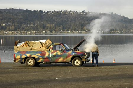 Old painted car with opened hood and a steam from boiling radiator
