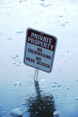 Private property sign misplaced in the ice covered lake