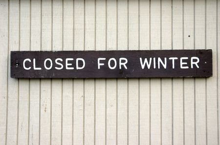 Closed for winter sign on a white wooden wall Stock Photo