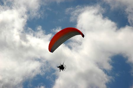 Powered parachute (PPC) in the sky with pilot and motor silhouette