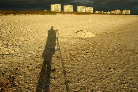 Shadow of a photographer with a tripod on a sandy beach of Marco Island, Florida photo