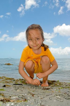 Girl drawing on the sand with a Sunshine Skyway bridge over Tampa Bay, Florida in background Stock Photo