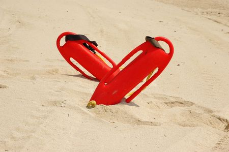 Two red patrol rescue cans stuck in sand