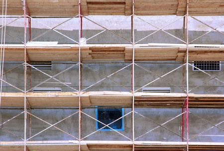 Metal rail and wooden toe-board scaffolds on a building, close-up photo