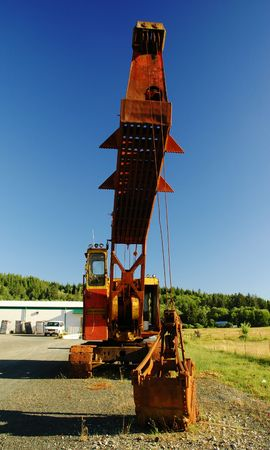 Old excavator with empty cabin, front view in percpective