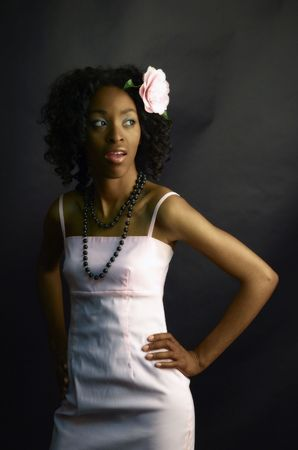 Portrait of beautiful african-american woman in pink dress, pink camellia in the hair and black beads Stock Photo - 3897344