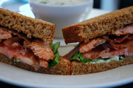pumpernickel: Halved grilled salmon sandwich on a pumpernickel bread  and a cup of soup close-up, shallow DOF Stock Photo