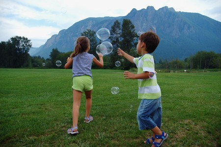 Girl and boy at the meadow playing with soap bubbles