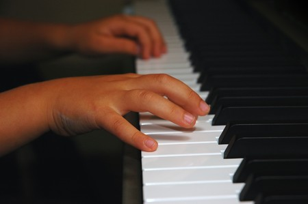 Close up of child hands playing piano Stock Photo - 4188921