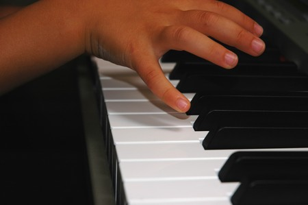 Close up of child hands playing piano Stock Photo - 4188920