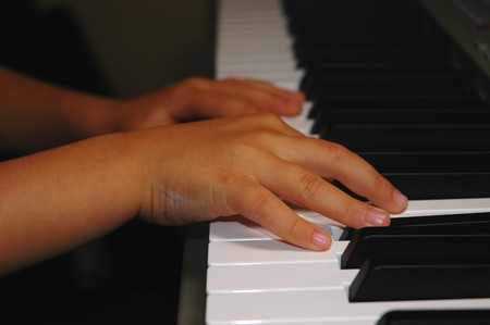 Close up of child hands playing piano