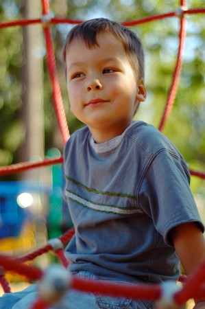 settled: Little boy settled down on a playground dreaming of something pleasant. Stock Photo
