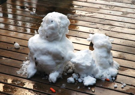 Snowmen melted in thaw on wooden deck