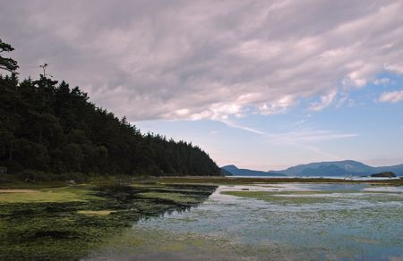 spencer: Big cloud above the saltchuck lagoon at Spencer Spit state park, Lopez Island Stock Photo