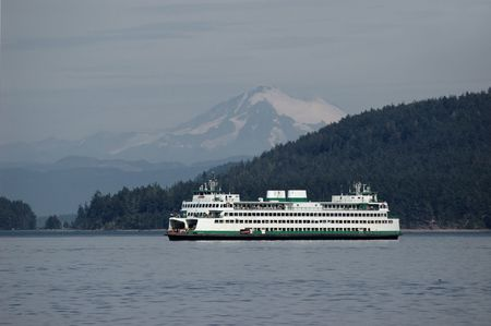 Ferry sailing through Puget sound with Mt. Baker on a background Stock Photo