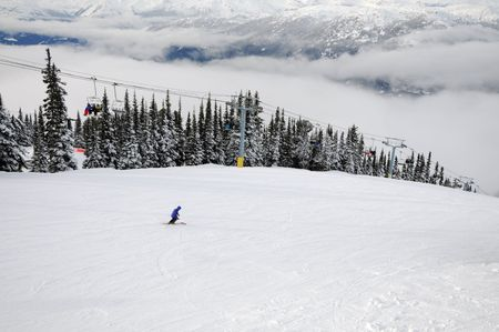 Skier going down the hill and people riding a chairlift at Whistler-Blackcomb ski resort in Canada Stock Photo - 6388194
