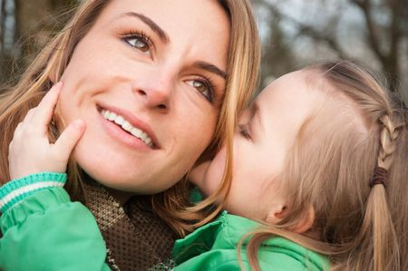 Young caucasian mother listens her toddler daughter whispering with smile Stock Photo