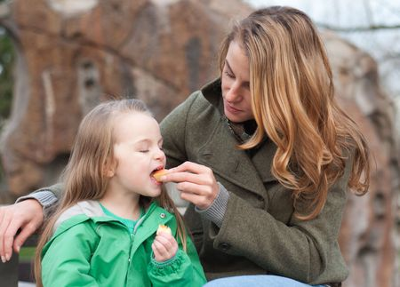 Little girl biting an apple from her mothers hands on a bench at the park