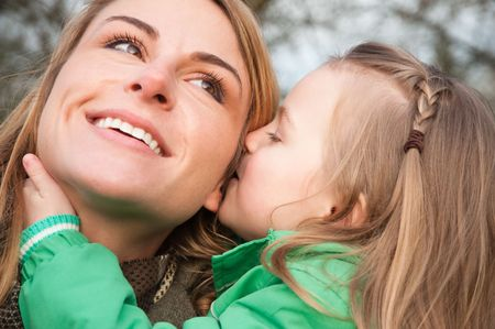 Young caucasian mother listens her toddler daughter whispering with smile photo