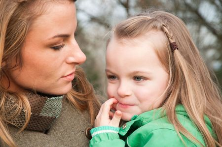 Puzzled blonde little girl in green jacket held by her mother Stock Photo - 6550165