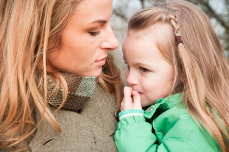 Little girl on mother's hands with pointer finger by her lips Stock Photo - 6550175