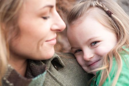 Shy smiling little girl on mothers hands, shallow DOF, focus on daughter photo