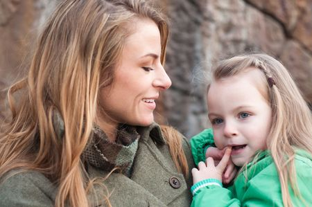 Smiling young woman holding her daughter, shallow DOF, focus on daughter photo