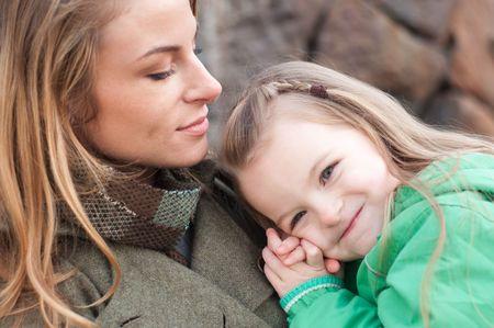 Happy toddler girl in a green jacket resting on moms shoulder photo