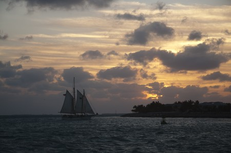 A schooner at sunset on a cloudy day on waters of Gulf of Mexico photo