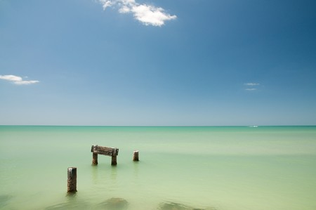 key of paradise: Remains of an old pier in the water right off the coast at Naples beach