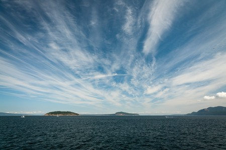 Strands of cirrus clouds above the water