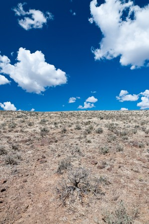 White fluffy clouds on bright blue sky  over the hill in Eastern Washington