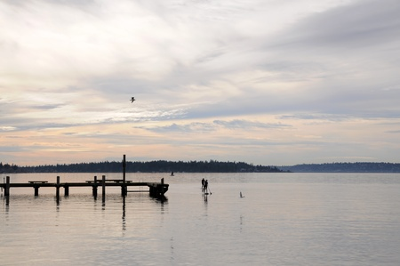 Two persons paddle boarding on Lake Washington on a cloudy day Stock Photo