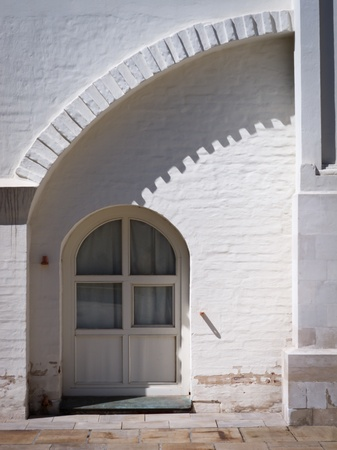 Architectural elements of an old white painted brick building with arch. photo