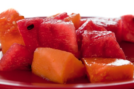 Isolated red plate with chunks of watermelon and papaya photo
