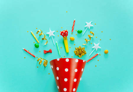 Happy birthday background: party hat, serpentine, stars, cocktail tubes, candles, blower on a yellow background.