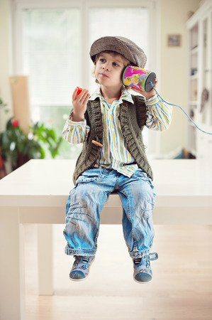 boy sitting: Cute little boy in vintage outfit sitting on a table and eating strawberry while playing with a tin can telephone Stock Photo