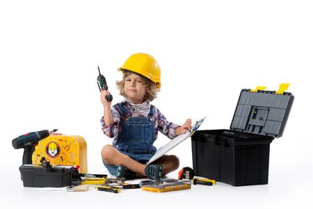 albañil: niño vestido como trabajador de servicio con casco protector tratando de entender cómo funciona el ou de perforación Foto de archivo