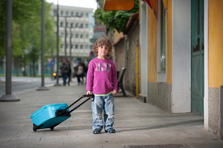lonesome: Cute little boy with a luggage bag on the street. Cute little boy with a luggage bag on the street. Growing up and becoming independent. Stock Photo