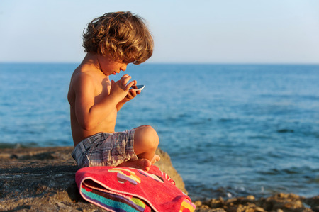 modern generation: Little boy playing with a smartphone on the beach. Modern lifestyle, modern generation concept. Stock Photo
